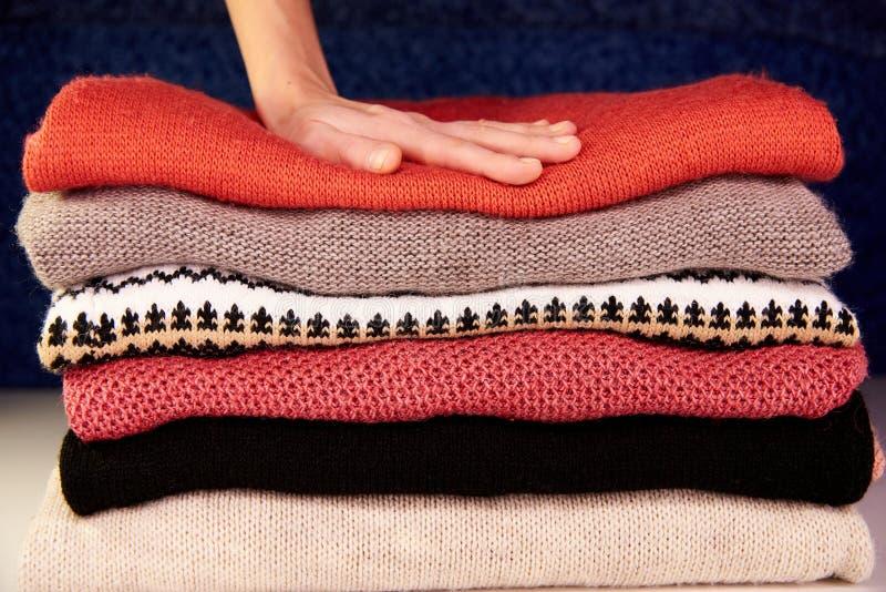 A mão toca em coisas de lã mornas imagem de stock