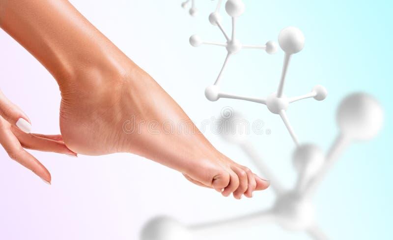 A mão toca no pé perto das moléculas brancas fotos de stock royalty free