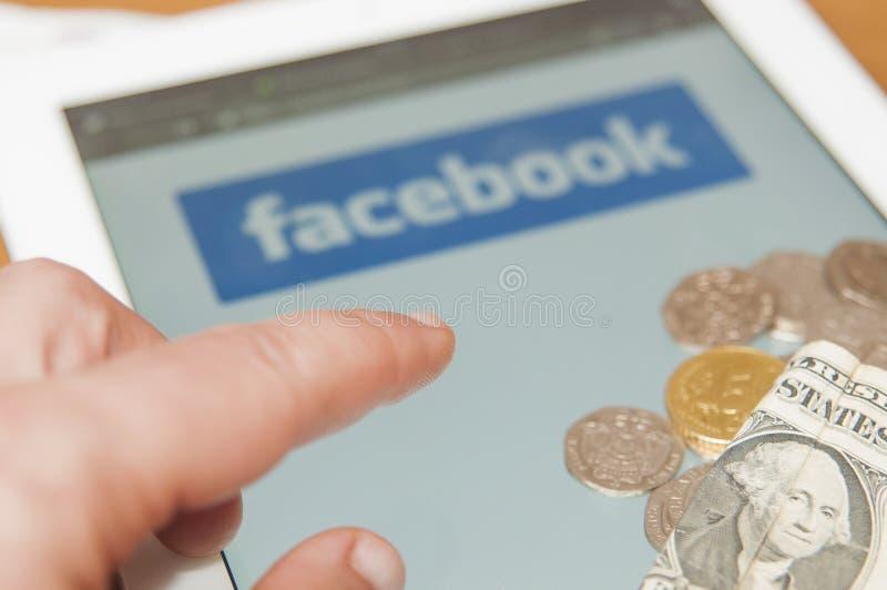 A mão toma o dinheiro de um grupo da moeda em um portátil com logotipo de Facebook Facebook anuncia o cryptocurrency global novo  fotografia de stock