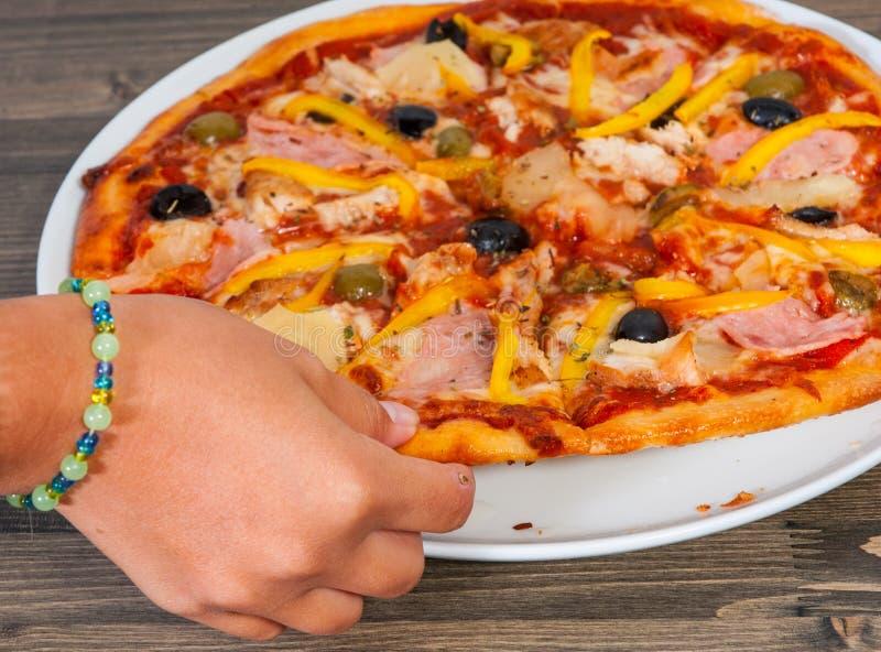 A mão toma uma parte de pizza havaiana fotografia de stock
