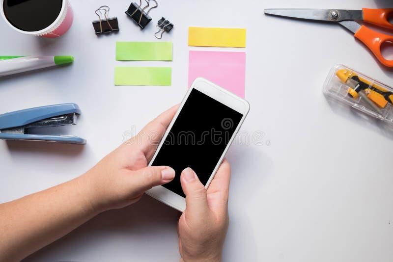Mão usando o smartphone na mesa de escritório fotografia de stock