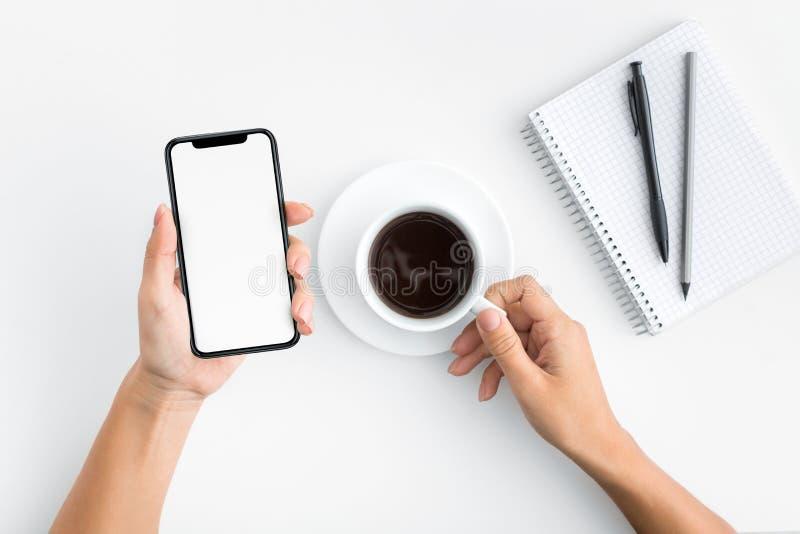 Mão usando o smartphone no fundo de madeira branco imagem de stock