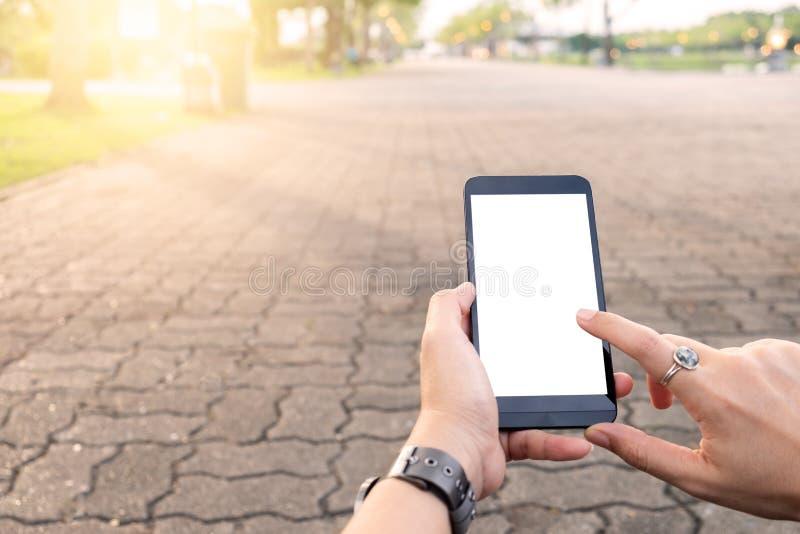 Mão usando a rua urbana do telefone celular imagem de stock
