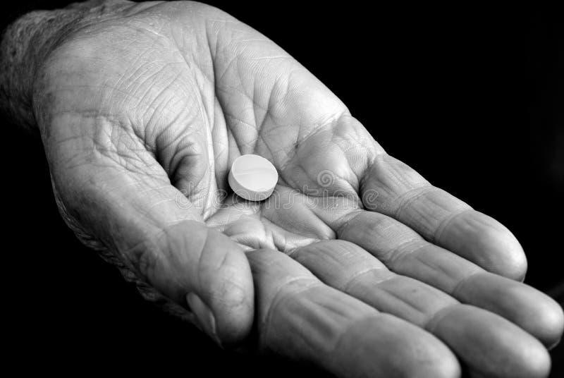 Mão velha com comprimido imagens de stock
