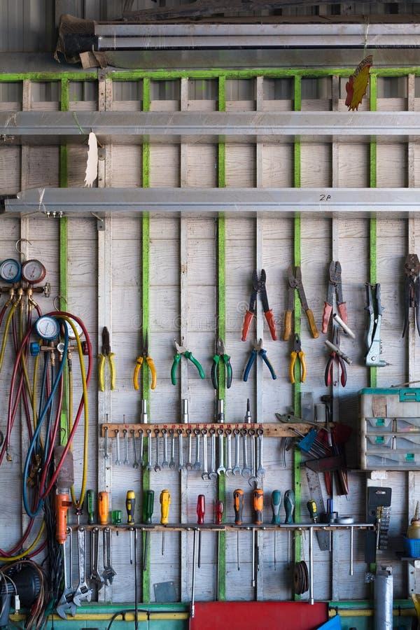 A mão velha utiliza ferramentas a suspensão na parede na oficina ou no auto garag do serviço fotografia de stock