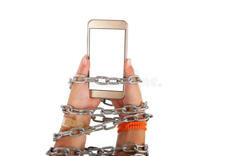 Mãos acorrentadas que guardam um smartphone fotos de stock royalty free