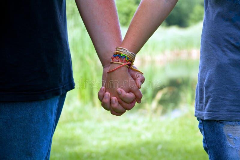 Mãos adolescentes da terra arrendada dos pares da idade, amor do verão fotos de stock royalty free