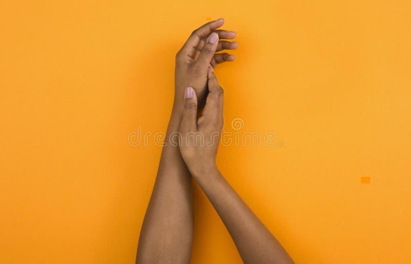 M?os afro-americanos da mulher que aplicam o creme hidratando imagem de stock