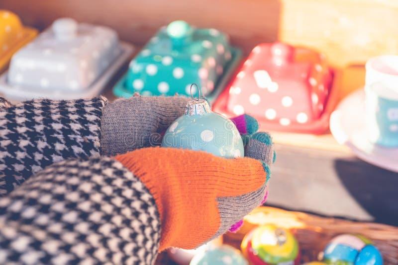 Mãos amadas de uma mulher segurando um brinquedo de Natal cerâmico com pontos no mercado sazonal da rua fotografia de stock