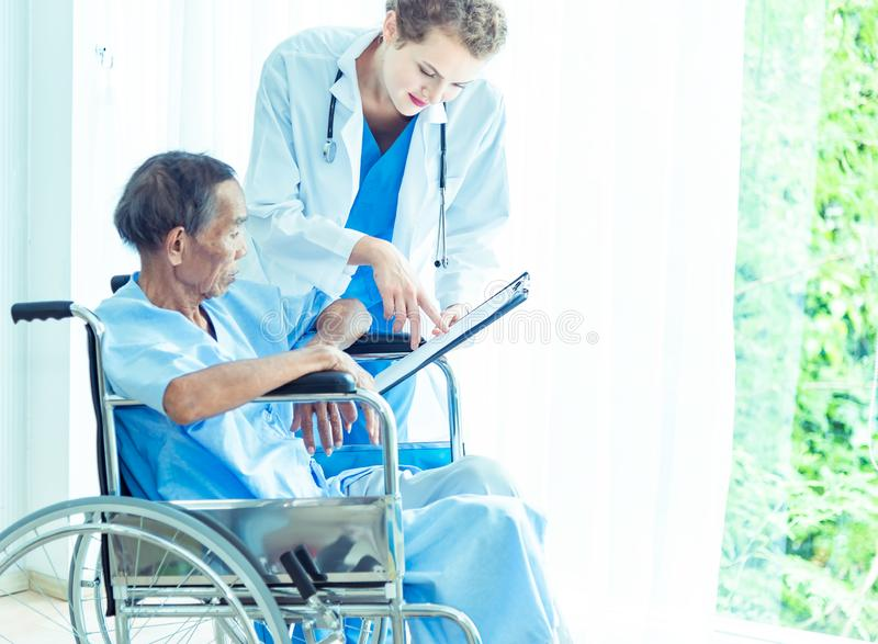 Mãos amiga fêmeas profissionais novas do doutor, explicando o diagnóstico ao paciente do homem superior no escritório médico fotografia de stock royalty free