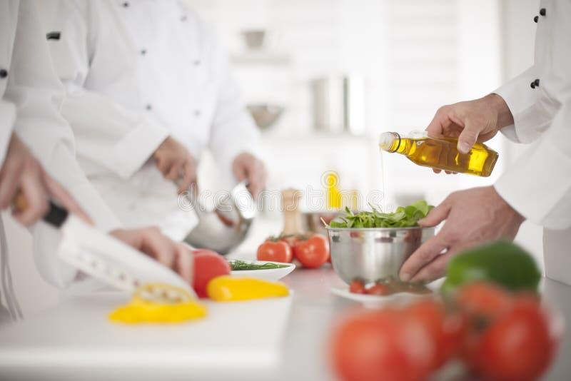 Mãos anônimas que preparam o alimento na cozinha profissional fotos de stock royalty free