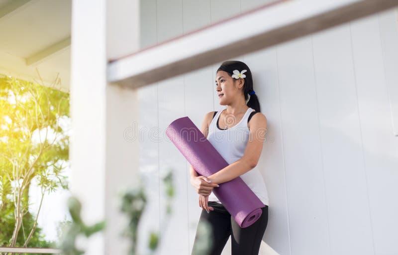 M?os asi?ticas ativas da mulher que guardam a esteira da ioga ap?s uma aptid?o do exerc?cio, do equipamento do exerc?cio, os feli fotografia de stock