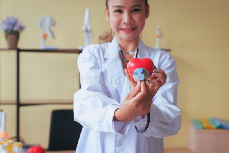 Mãos asiáticas da mulher do doutor que guardam o modelo vermelho do estetoscópio e do coração, feliz e sorrindo, foco seletivo fotografia de stock royalty free