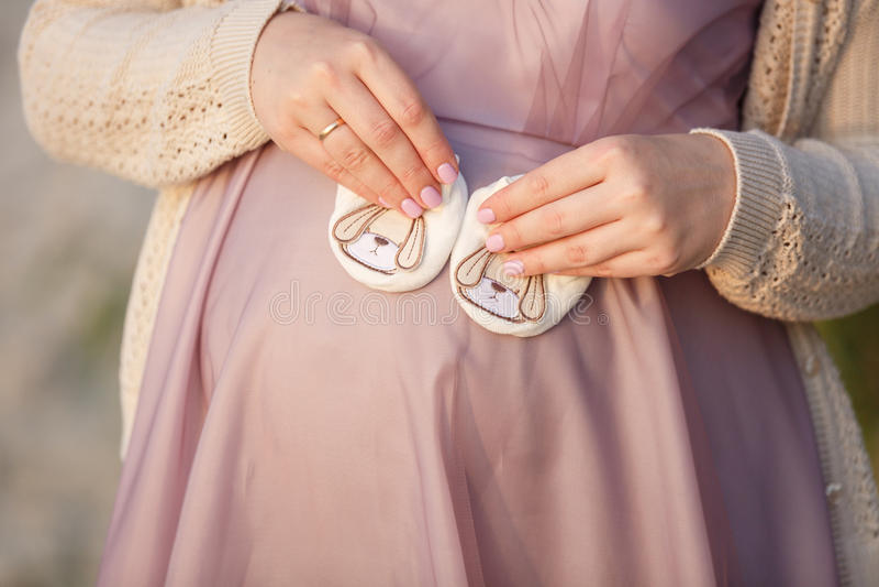 Mãos bebê, ` s da mamãe e do ` de espera s do paizinho em uma barriga foto de stock