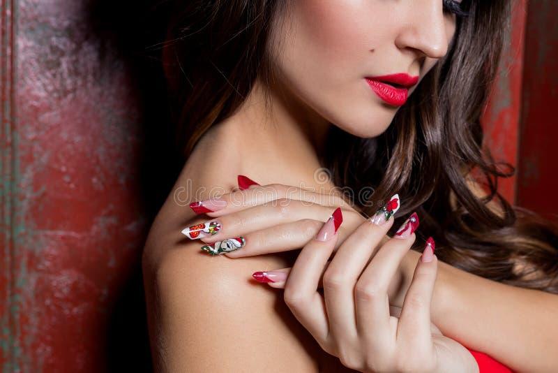 Mãos bem arrumados bonitas de uma moça com os pregos acrílicos falsificados longos com um teste padrão festivo do Natal nos prego foto de stock royalty free