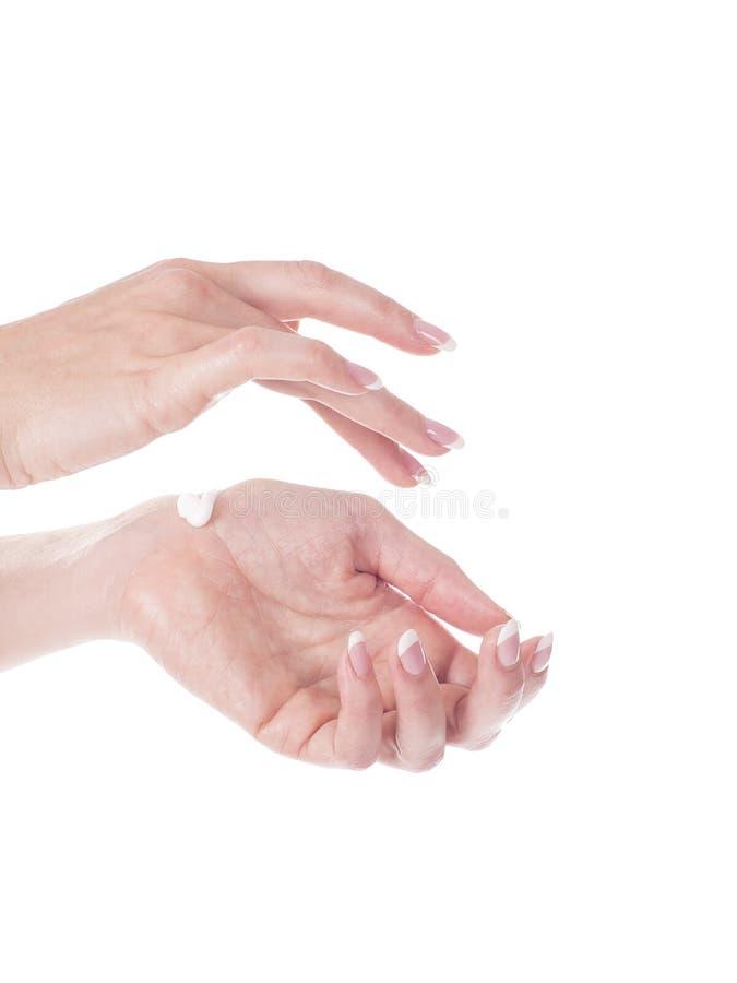 Mãos bonitas da jovem mulher com o creme, isolado no branco imagem de stock