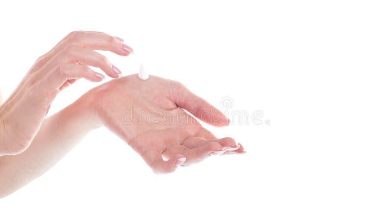 Mãos bonitas da jovem mulher com o creme, isolado no branco imagens de stock royalty free