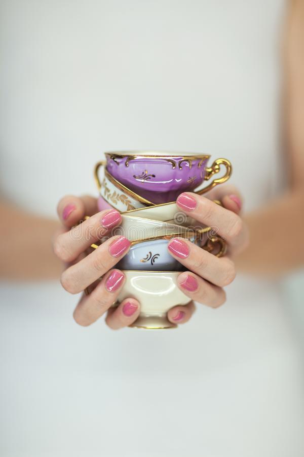 Mãos bonitas da mulher com o verniz para as unhas cor-de-rosa perfeito que guarda poucos copos de chá do vintage foto de stock