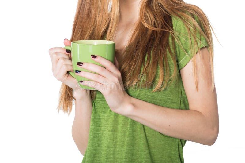 Mãos bonitas da mulher que guardam o copo de café verde foto de stock royalty free