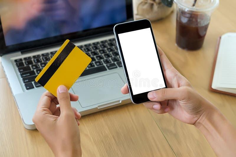 Mãos bonitas da mulher que guardam um cartão de crédito fotos de stock royalty free