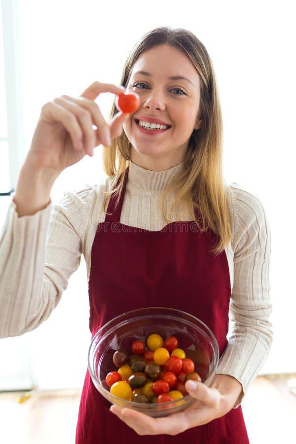 Mãos bonitas de sorriso da mulher que guardam tipos diferentes de tomates de cereja na bacia redonda em casa fotografia de stock royalty free