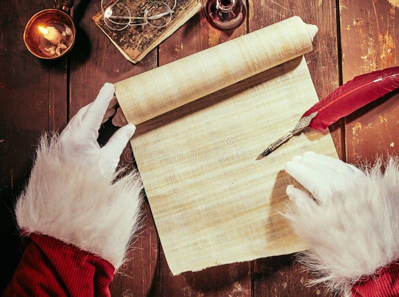 Mãos cobertas do pai Christmas que escrevem em um rolo do pergaminho do vintage com uma pena da pena pela luz de vela com espaço  fotografia de stock