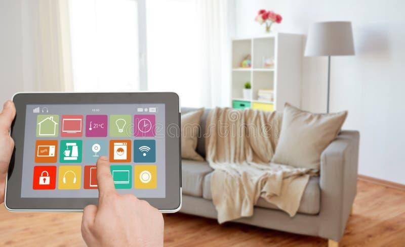 Mãos com ícones espertos da casa no tablet pc fotografia de stock royalty free