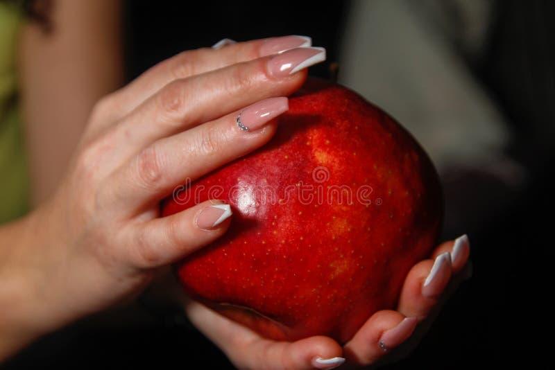 Mãos com artes do prego nos pregos que guardam a maçã vermelha grande foto de stock royalty free