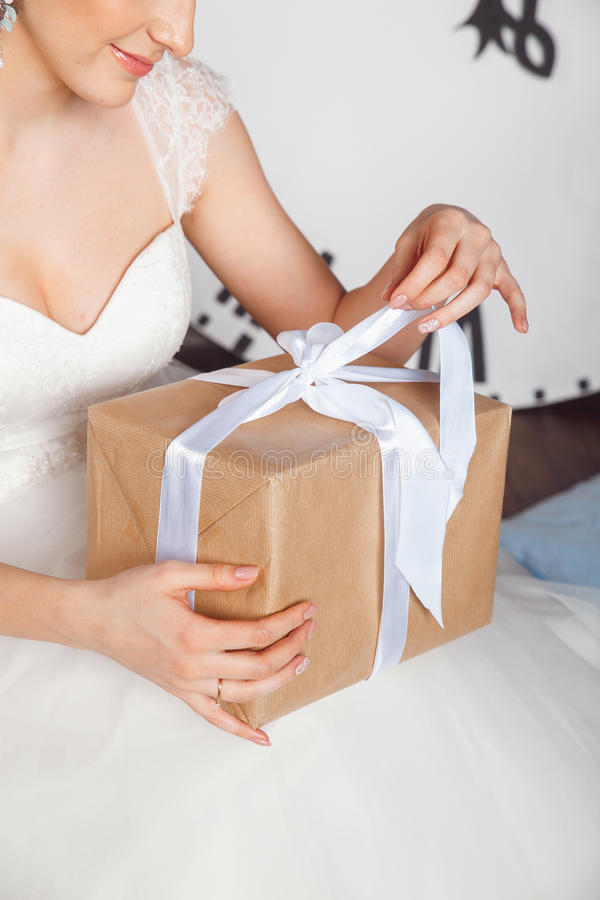 Mãos com a caixa de presente na celebração do casamento Retratos do estúdio da noiva bonita com presente Noiva que guarda o prese imagens de stock royalty free