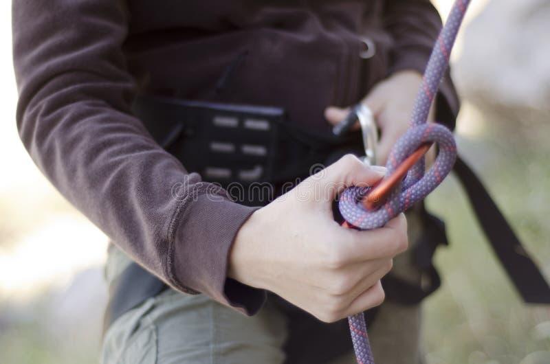 Mãos com corda e a engrenagem de escalada fotografia de stock