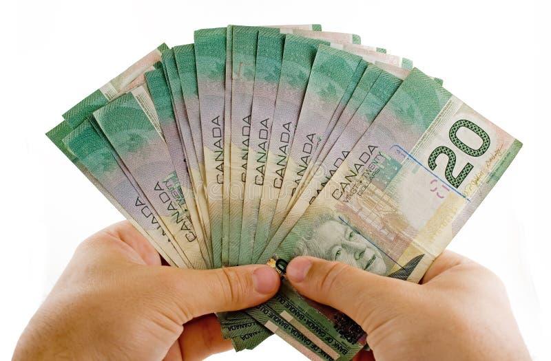 Mãos com dólares canadianos foto de stock royalty free