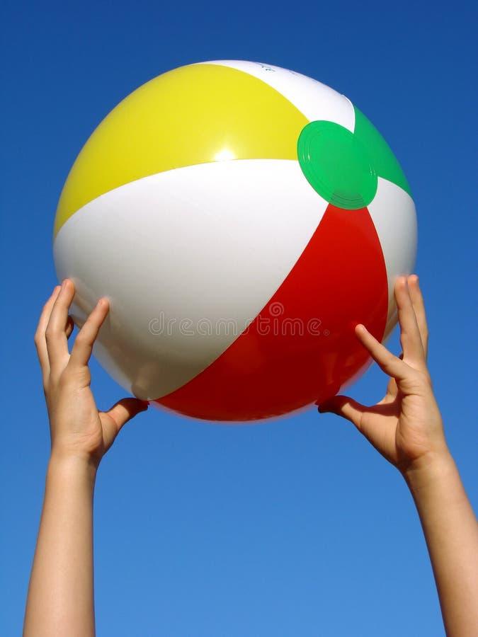 Mãos com esfera de praia imagens de stock