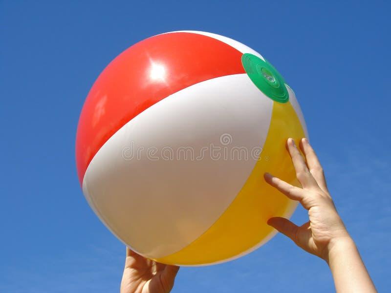 Mãos com esfera de praia fotografia de stock