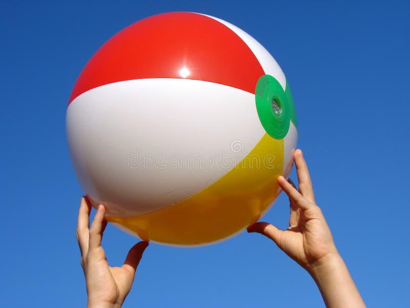 Mãos com esfera de praia imagens de stock royalty free