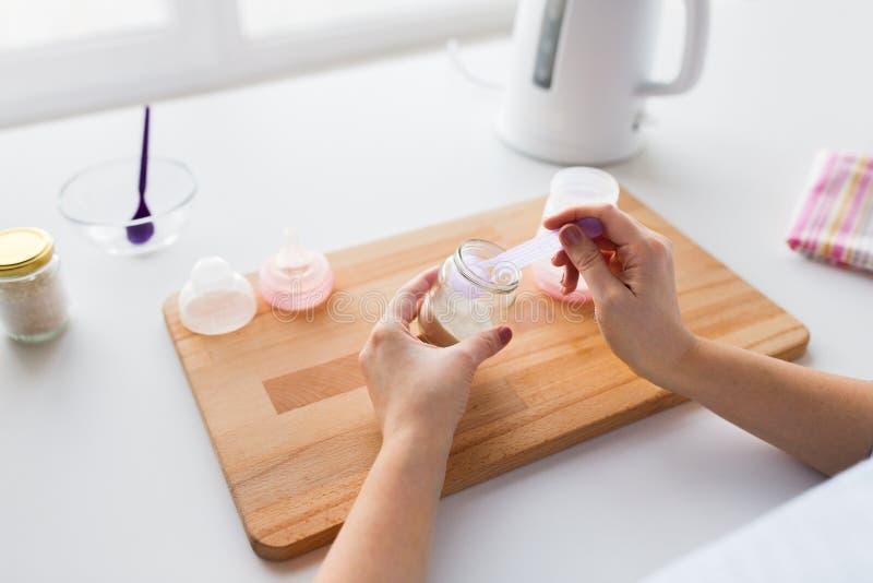 Mãos com a fórmula infantil que faz o leite do bebê foto de stock royalty free