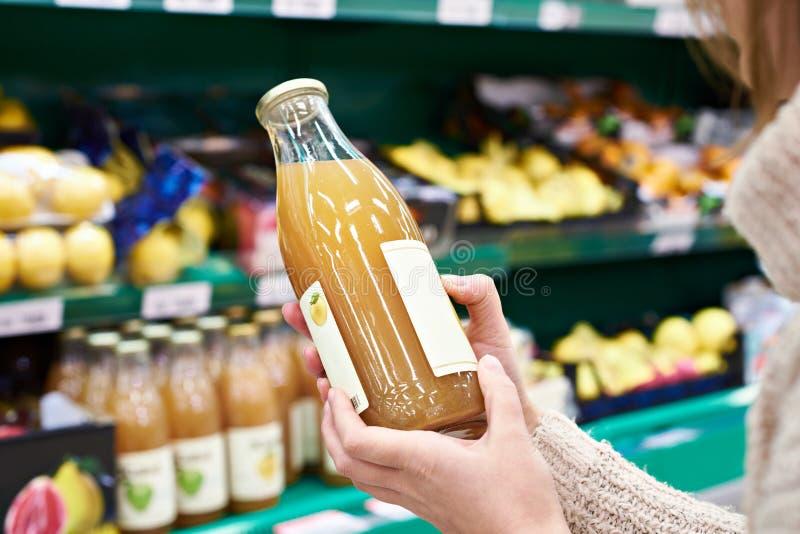 Mãos com a garrafa do suco de maçã fresco na loja imagens de stock royalty free