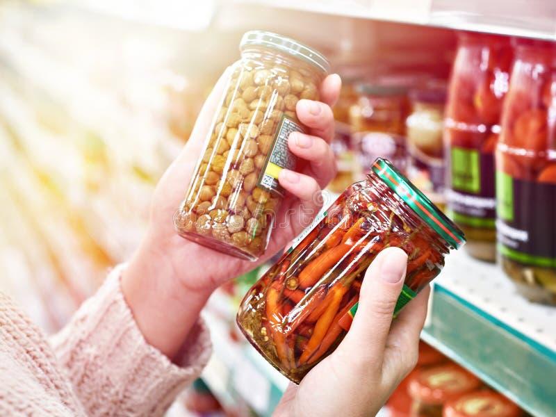 Mãos com a lata de alcaparras enlatadas e de pimentas vermelhas quentes foto de stock