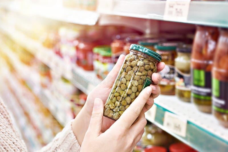 Mãos com a lata de alcaparras enlatadas na loja fotografia de stock