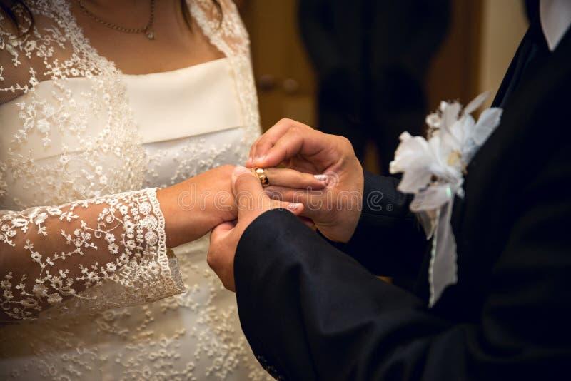Mãos com o noivo dos anéis que põe o anel dourado fotografia de stock royalty free