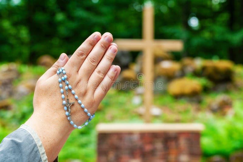 Mãos com o rosário que reza perto da cruz em exterior imagens de stock royalty free