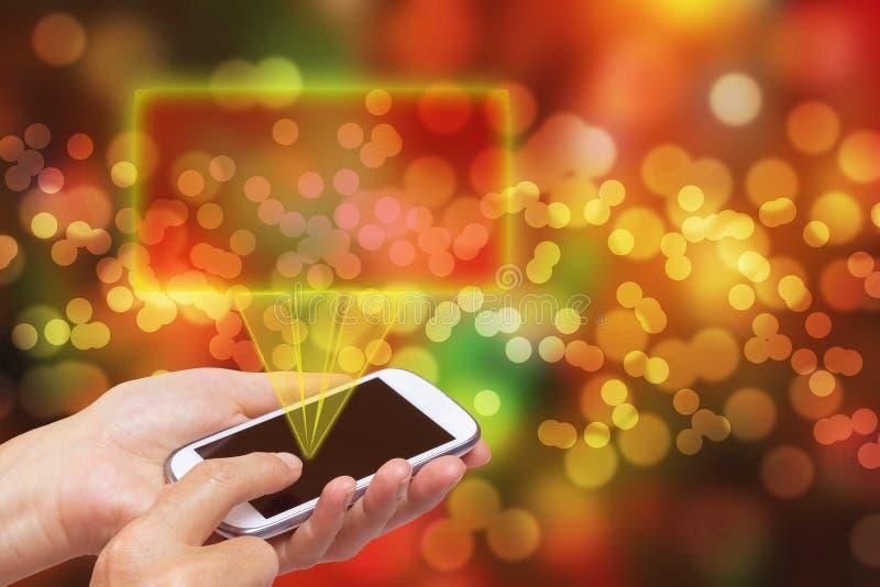 Mãos com o telefone esperto no fundo abstrato do Natal fotos de stock