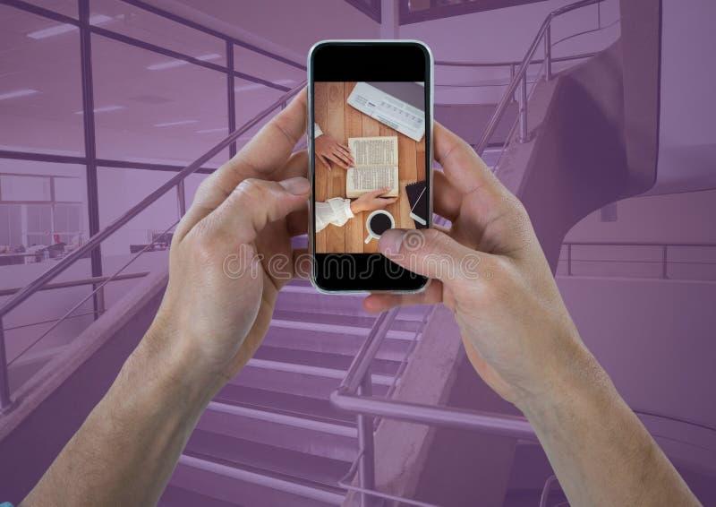 Mãos com o telefone que mostra a mesa contra escadas com folha de prova roxa fotografia de stock