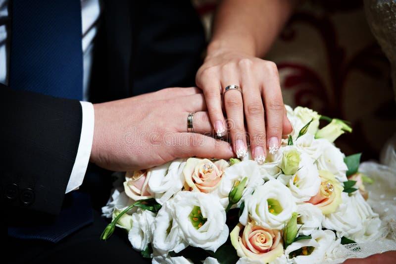 Mãos com os newlyweds felizes dos anéis de ouro do casamento imagem de stock royalty free