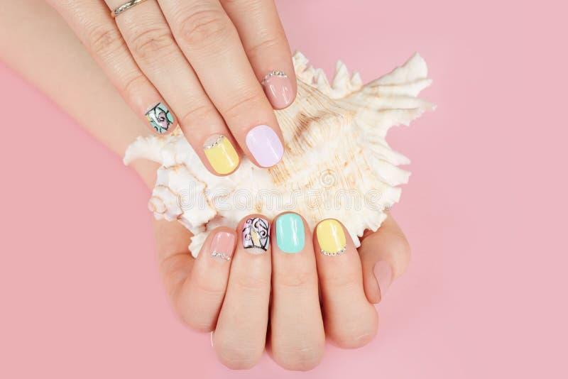 Mãos com os pregos e shell manicured bonitos do mar fotos de stock