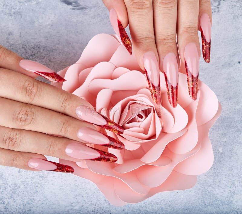 Mãos com os pregos manicured franceses artificiais vermelhos longos e a flor cor-de-rosa cor-de-rosa foto de stock