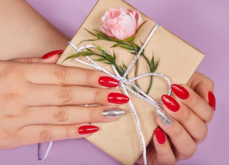 Mãos com os pregos manicured franceses artificiais vermelhos que guardam uma caixa de presente imagens de stock royalty free