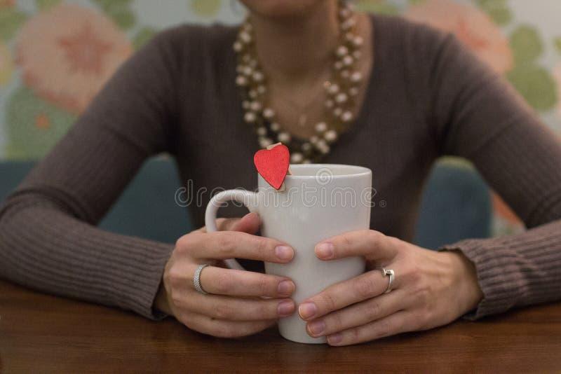 mãos com um copo e um coração foto de stock
