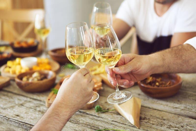 Mãos com vidros de vinho branco imagens de stock royalty free