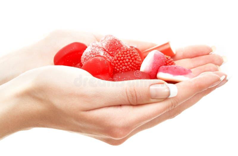 Mãos completamente de bombons vermelhos fotografia de stock
