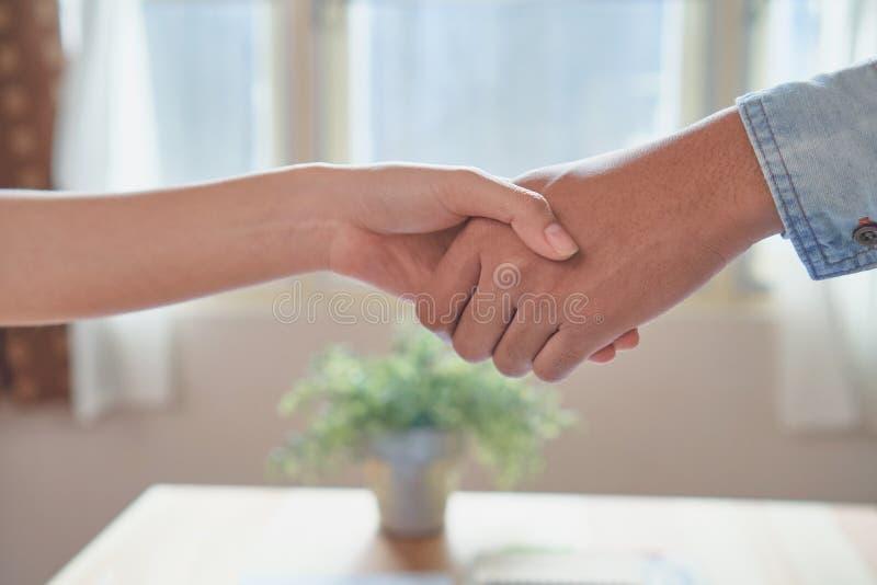Mãos comum de dois homens de negócios após ter negociado um acordo bem sucedido do negócio, e o aperto de mão junto imagens de stock